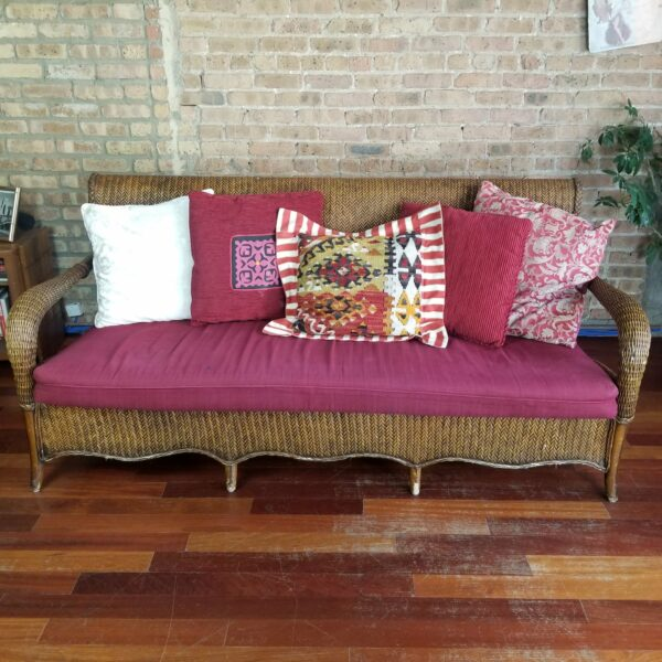 Pictured, Brown Wicker Three-Seater with Red Cushion and 5 various matching decorative pillows, among the vintage rental furniture from Catalyst Ranch