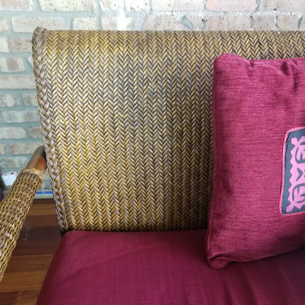 Pictured, Close up of wicker pattern on Brown Wicker Three-Seater with Red Cushion, among the vintage rental furniture from Catalyst Ranch
