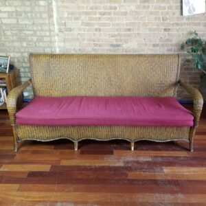 Pictured, Brown Wicker Three-Seater with Red Cushion, among the vintage rental furniture from Catalyst Ranch