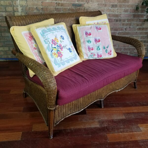 Pictured, Brown Wicker Two-Seater with Red Cushion and four yellow and white floral pattern decorative pillows, among the vintage rental furniture from Catalyst Ranch