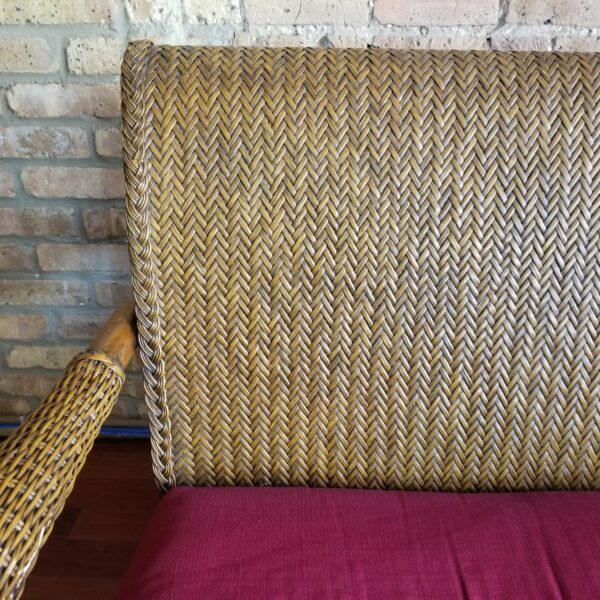 Pictured, Close up of wicker pattern on Brown Wicker Two-Seater with Red Cushion and four yellow and white floral pattern decorative pillows, among the vintage rental furniture from Catalyst Ranch