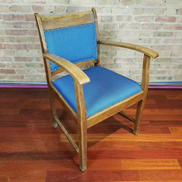 Pictured, wood dining armchair with blue studded fabric, among the vintage rental furniture from Catalyst Ranch