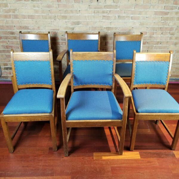 Pictured, set of 6 wood dining chairs with blue studded fabric, among the vintage rental furniture from Catalyst Ranch