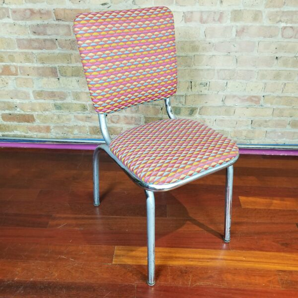 Pictured, tangy triangle red, pink, yellow, and blue fabric dining chair, among the vintage rental furniture from Catalyst Ranch