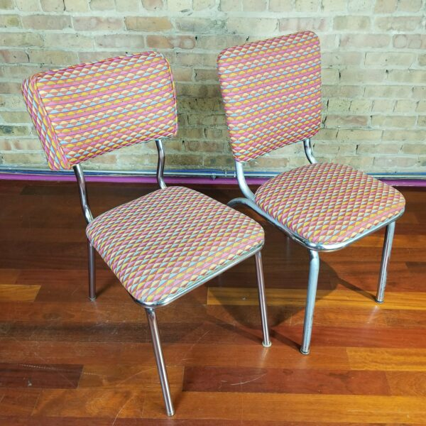 Pictured, pair of tangy triangle red, pink, yellow, and blue fabric dining chairs, among the vintage rental furniture from Catalyst Ranch