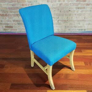 Pictured, plush blue fabric dining chair, among the vintage rental furniture from Catalyst Ranch