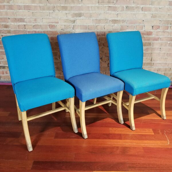 Pictured, trio of plush blue fabric dining chairs, among the vintage rental furniture from Catalyst Ranch