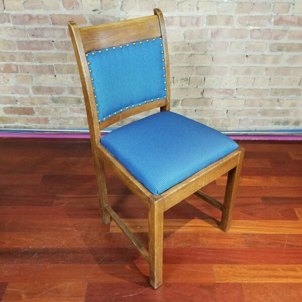 Pictured, wood dining chair with blue studded fabric, among the vintage rental furniture from Catalyst Ranch
