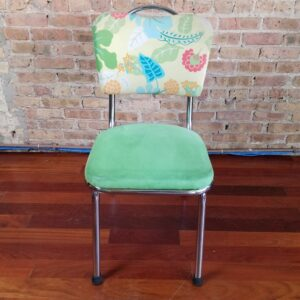 Pictured, metal framed dining chair with green plush seat and garden flora pattern, among the vintage rental furniture from Catalyst Ranch