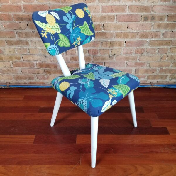 Pictured, Blue Exotic Leaves Dining Chair with white wood legs and frame, one of a set of four to be rented in pairs, among the vintage rental furniture available from Catalyst Ranch