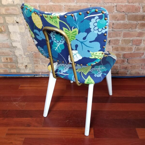 Pictured, Rear view of metal back on one of Blue Exotic Leaves Dining Chair with white wood legs and frame, one of a set of four to be rented in pairs, among the vintage rental furniture available from Catalyst Ranch