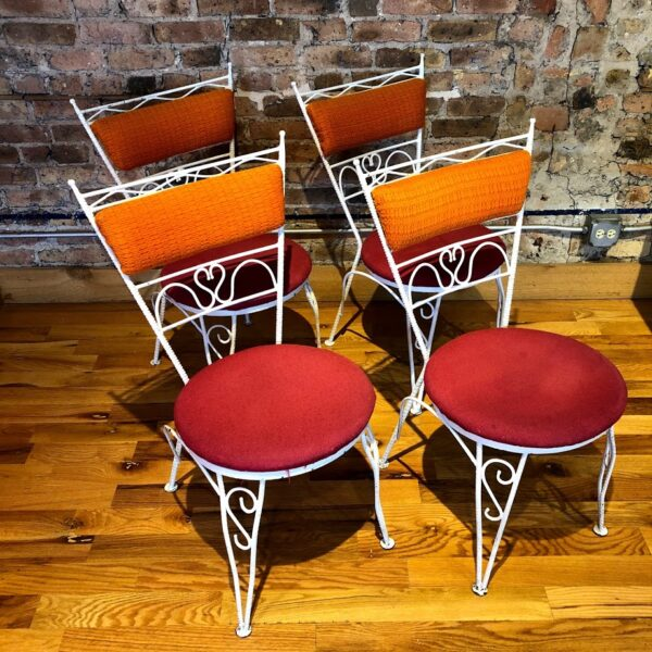 Pictured, set of four white metal dining chairs with various whimsical detailing, red plush seats and orange plush backs, can be rented in pairs, among the vintage rental furniture from Catalyst Ranch