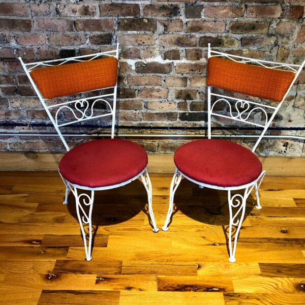 Pictured, pair white metal dining chairs with various whimsical detailing, red plush seats and orange plush backs, part of a set of 4 that can be rented in pairs, among the vintage rental furniture from Catalyst Ranch