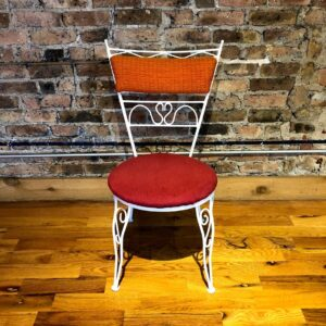 Pictured, white metal dining chair with various whimsical detailing, red plush seat and orange plush back, part of a set of 4 that can be rented in pairs, among the vintage rental furniture from Catalyst Ranch