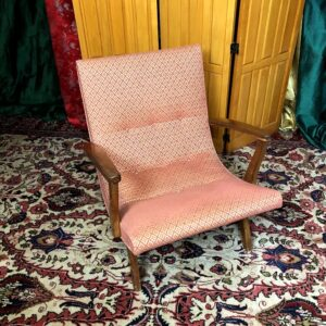 Pictured, pink fabric low lounge armchair with diamond patterning, among the vintage rental furniture from Catalyst Ranch