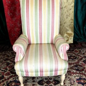 Pictured, pink, green, yellow and white pastel striped high back armchair, among the vintage rental furniture from Catalyst Ranch