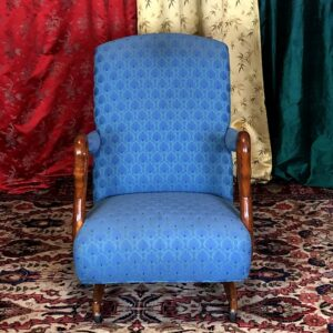 Pictured, Ocean Blue upholstered rolling chair with wooden swan hand rests, among the vintage rental furniture from Catalyst Ranch