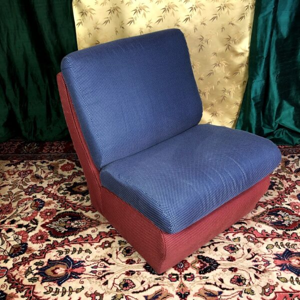 Pictured, red base, blue seat, color block plush cushion low chair, rented as a set, among the vintage rental furniture available from Catalyst Ranch