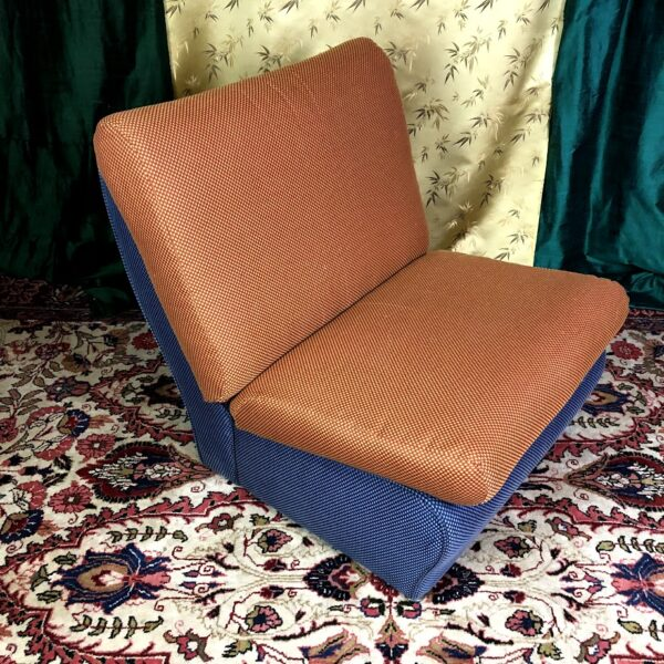 Pictured, blue base, orange seat, color block plush cushion low chair, rented as a set, among the vintage rental furniture available from Catalyst Ranch