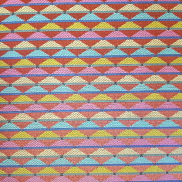 Pictured, close up of tangy triangle fabric in orange, green, blue, yellow and pink, among the vintage rental furniture from Catalyst Ranch