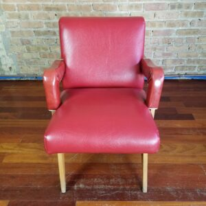 Pictured, Curvy Red Vinyl Low Armchair, among the vintage rental furniture from Catalyst Ranch