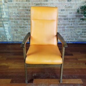 Pictured, Orange Vinyl High back Armchair, among the vintage rental furniture from Catalyst Ranch