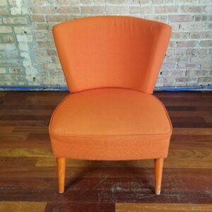 Pictured, plush Tangerine Fabric Low Chair, among the vintage rental furniture from Catalyst Ranch