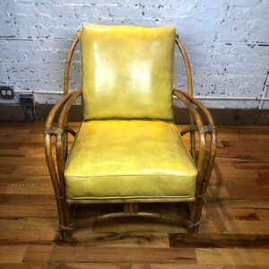 Pictured, Sunflower Yellow Vinyl and Bamboo Armchair, among the vintage rental furniture from Catalyst Ranch