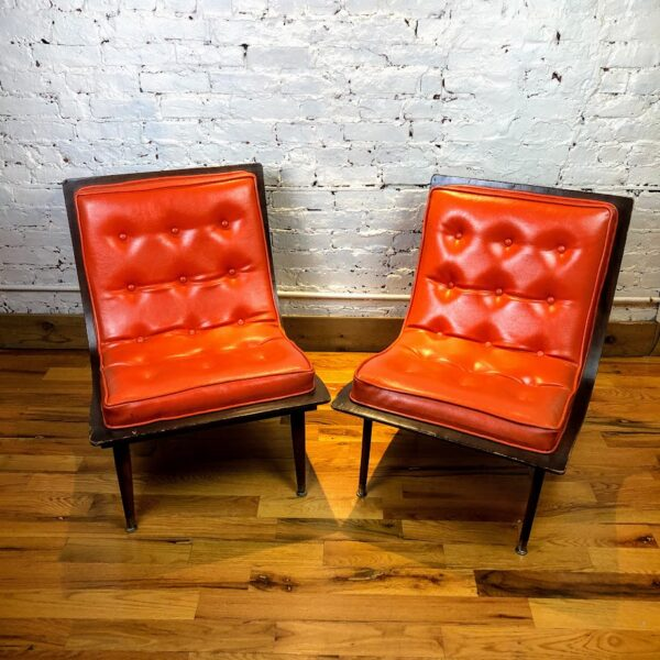 Pictured, Pair of Orange Vinyl Curved Wood Low Chairs, among the vintage rental furniture from Catalyst Ranch