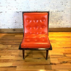Pictured, Orange Vinyl Curved Wood Low Chair. One of a pair among the vintage rental furniture from Catalyst Ranch