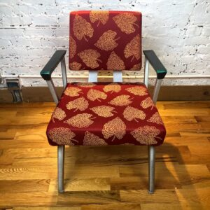 Pictured, Armchair with maroon fabric and golden leaf patterns, among the vintage rental furniture available from Catalyst Ranch