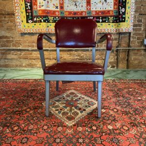 Pictured, Oxblood Red Vinyl Office Armchair sat atop red abstract Oriental rug, among the vintage rental furniture available from Catalyst Ranch