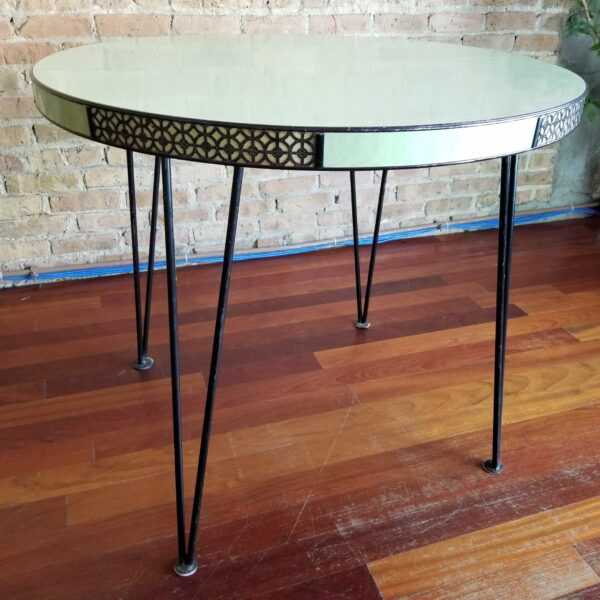 Pictured, pale green round Formica dining table with lattice side details, among the vintage rental furniture from Catalyst Ranch