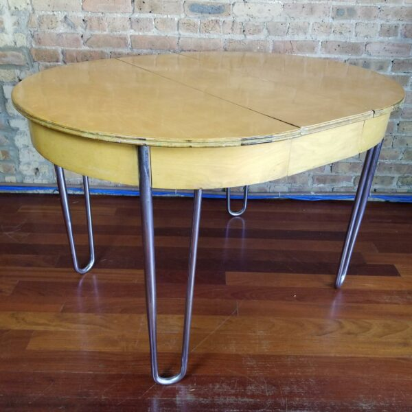 Pictured, oval wood dining table with metal legs, among the vintage rental furniture from Catalyst Ranch