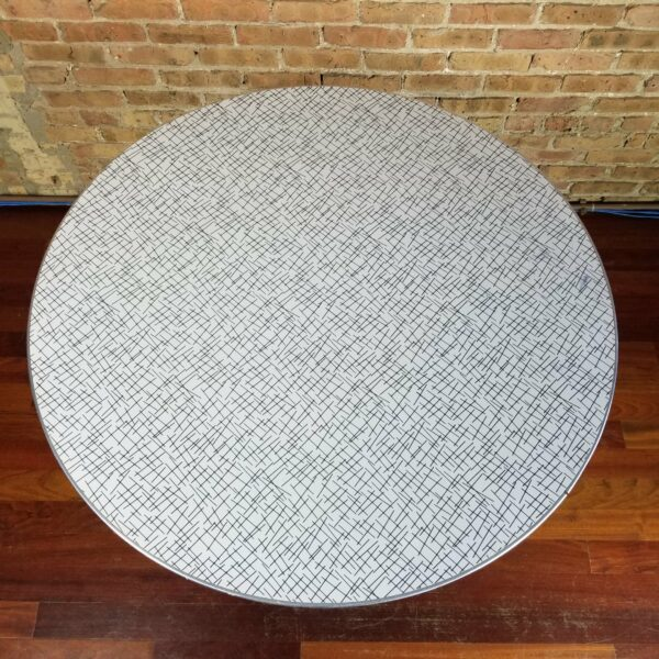Pictured, top down view of round Formica dining table with crosshatch pattern, among the vintage rental furniture from Catalyst Ranch