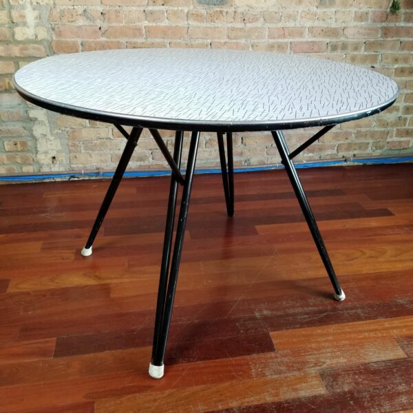 Pictured, round Formica dining table with crosshatch pattern, among the vintage rental furniture from Catalyst Ranch