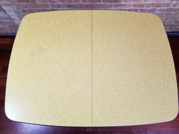 Pictured, top down view of yellow Formica dining table, among the vintage rental furniture from Catalyst Ranch