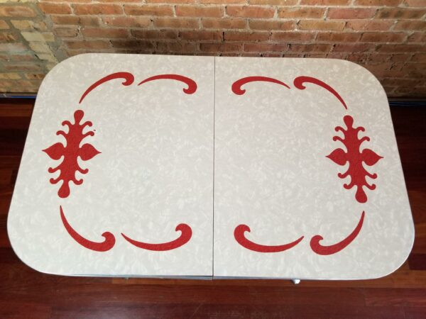 Pictured, top down view of White Formica dining table with Red swirl details, among the vintage rental furniture from Catalyst Ranch
