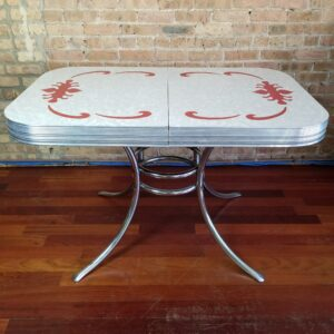 Pictured, White Formica dining table with Red swirl details, among the vintage rental furniture from Catalyst Ranch