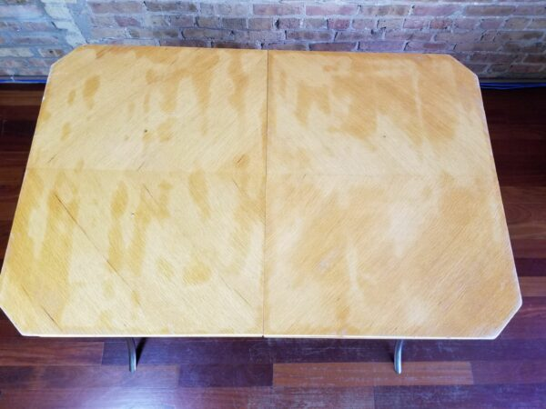 Pictured, top down view of blonde wood dining table with curved metal legs, among the vintage rental furniture from Catalyst Ranch