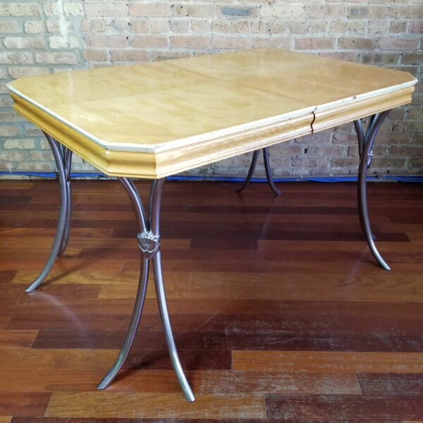 Pictured, blonde wood dining table with curved metal legs, among the vintage rental furniture from Catalyst Ranch