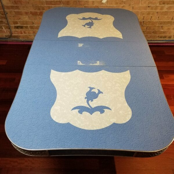 Pictured, Blue and white Formica table with Bellflower details and silver detailing on corners, among the vintage rental furniture from Catalyst Ranch