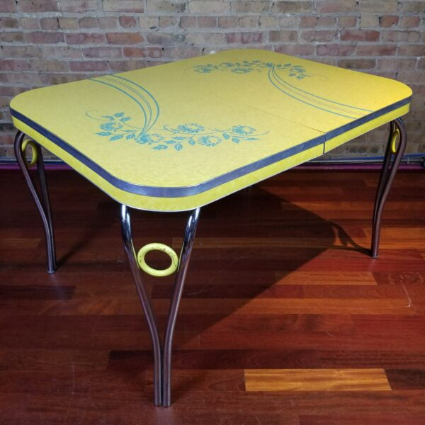 Pictured, Yellow Formica dining table with Blue floral details and metal legs with decorative yellow ring, among the vintage rental furniture from Catalyst Ranch