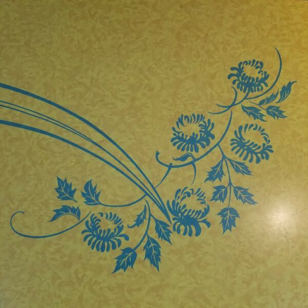 Pictured, Close up of blue floral leaf details on Yellow Formica dining table, among the vintage rental furniture from Catalyst Ranch