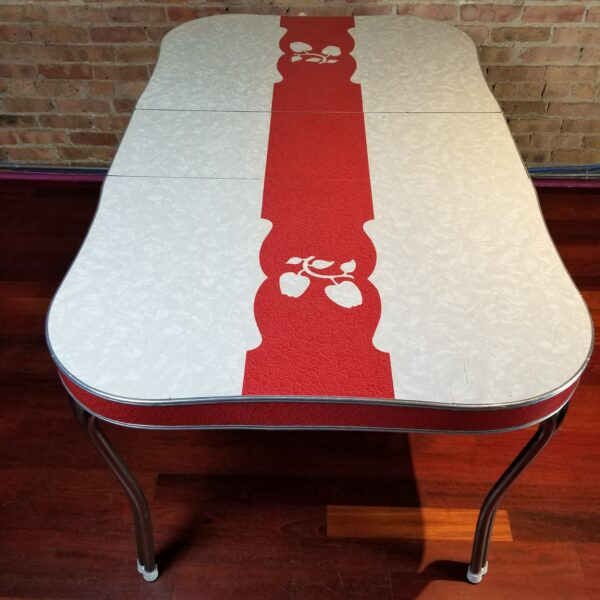 Pictured, Formica dining table with Red stripe and white apple details, among the vintage rental furniture from Catalyst Ranch
