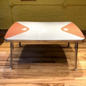 Pictured, Formica dining table with peach detailing and leaf details, among the vintage rental furniture from Catalyst Ranch