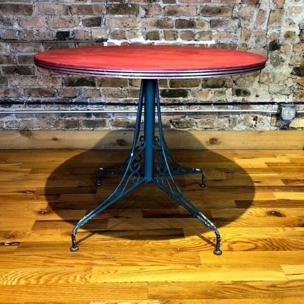 Pictured, Round Red Stained Wood Table with Metal Base, among the vintage rental furniture from Catalyst Ranch