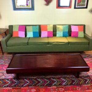 Pictured, Moss Green Mod style Long Couch with five multi color block decorative pillows, long dark wood coffee table, sat atop a colorful decorative rug, among the vintage rental furniture from Catalyst Ranch