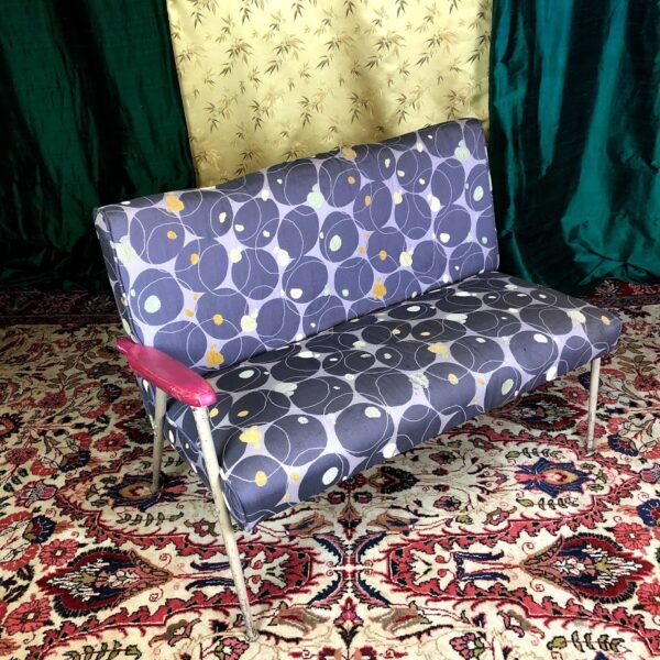 Pictured, Single-Arm Two-Seater couch with violet color and circle patterns, among the vintage rental furniture from Catalyst Ranch