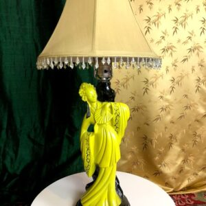 Pictured, beige shaded lamp with ornate yellow ceramic Asian woman in luxury, among the vintage rental furniture available from Catalyst Ranch